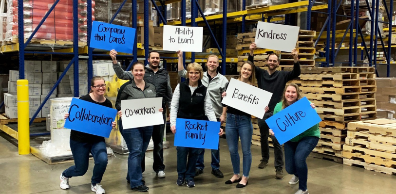 Employees holding signs in warehouse